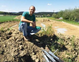 Jacobs is sitting on a pile of topsoil – very rich in humus – in front of the property that is going to be Wunderboden's new vegetable greenhouse. (Photo by the author)